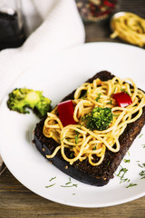 fried black bread with spaghetti and vegetables on a plate on a wooden table