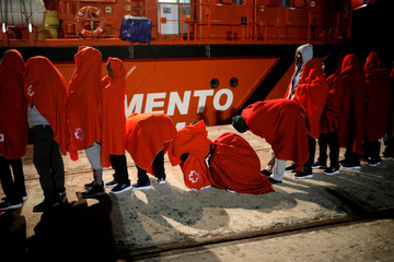 """Migrant women line up as they wait to embark the """"Mastelero"""" rescue vessel to sleep on it after disembarking the """"Caliope"""" rescue boat after arriving at the port of Malaga"""
