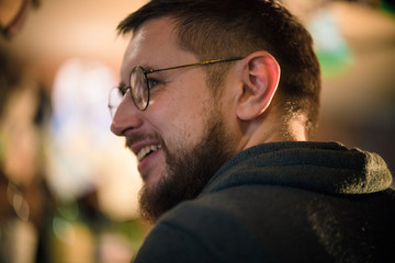 Bearded man in glasses looking to the side.