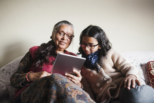 A young girl and a woman looking at a tablet together.