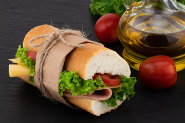 sandwich with with ham, cheese, tomatoes, lettuce on over stone