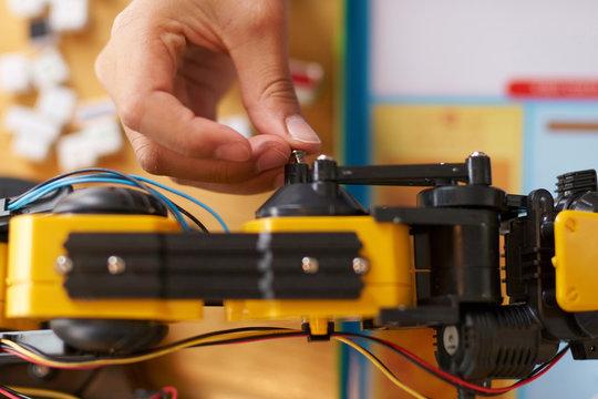Boy putting a screw into a robotic arm
