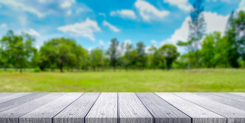 Wooden tabletop with green park nature blurred background
