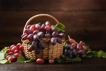 Ripe grapes in wicker basket on wooden background. Fototapete