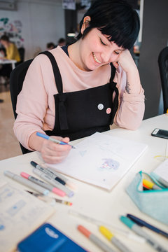 Shorthaired girl drawing a sketch at a coworking space