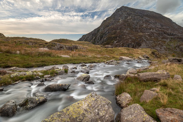 Moody landscape image of river flowing down mountain range near Llyn Ogwen and Llyn Idwal in Snowdonia in Autumn