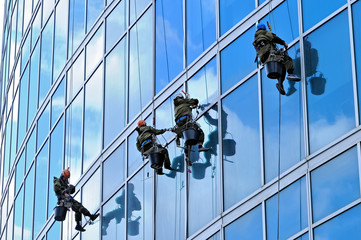 Industrial climbers wash windows of skyscraper