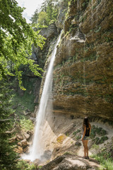 adventurous woman in the mountains looking at big waterfall