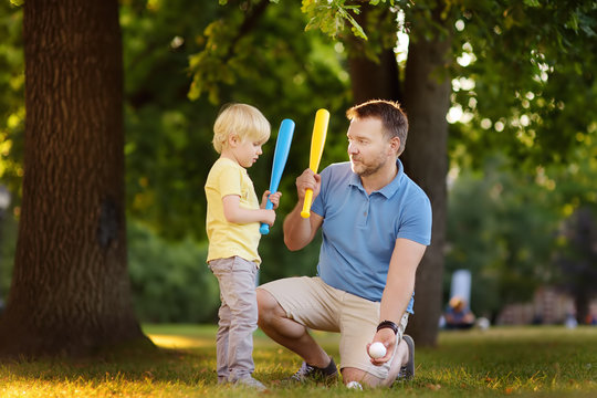 Father and his son playing baseball in park.