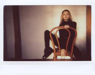Beautiful model in black sitting on chair