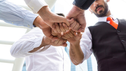 Closeup on hands. Colleague putting their hands on top of each other symbolizing unity and teamwork while doing activity outdoor. People joining hand together as a business goal achievement