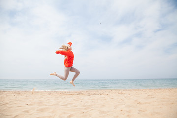joyful woman jumping on a sandy beach, Ocean