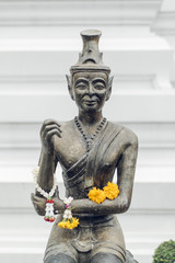 Statue of Buddha with flowers in a Thai temple