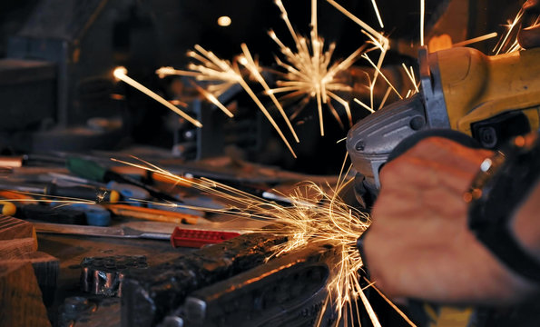 sparks made by using electric disc grinder polishing the surface metal
