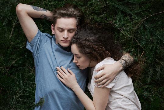 Asleep young couple on fir bed