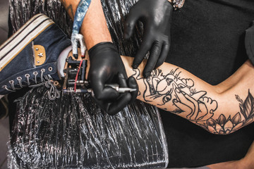 girl with dreadlocks in a tattoo parlor. The master creates a picture on the body of a young beautiful girl. Close-up of hands and tattoo machine
