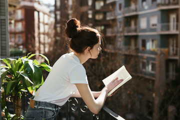 Side view of a young woman reading a book in a balcony.