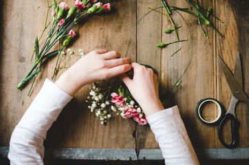 Hands of a child making a flower crown