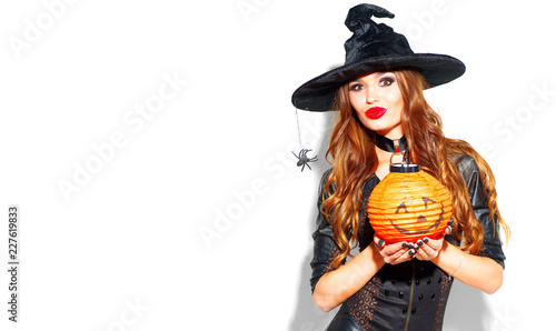 Halloween. Sexy witch with bright holiday makeup. Beautiful young woman posing in witches costume with pumpkin lantern over white background