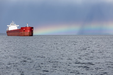 Anchored ship at bay with a rainbow