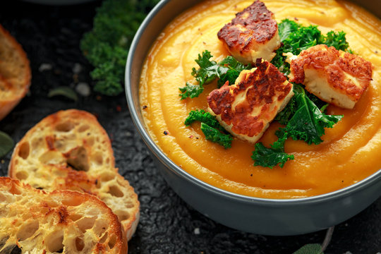 Baked butternut squash and carrot cream soup with steamed kale and fried halluomi