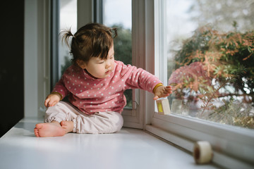 Little baby playing with blocks by window