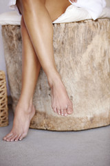 Hispanic woman's legs relaxing on wood stump stool in spa