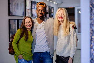 Team of three happy multi ethnic students, friends, one black man and two european women hugging indoor in art passage in gallery. Multi ethnic, different culture and friendship concept.