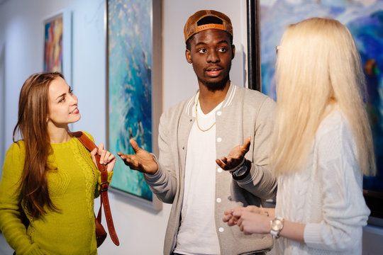 Young black hipster man talking and gesticulating with two girl friends in art photo gallery. Multi ethnic, shared values and culture friendship concept.