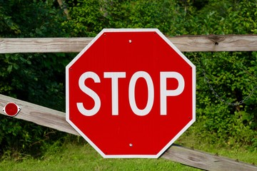 The red octagon stop sign on the wooden gate.
