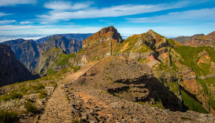 Madeira, Portugal. Tourists on a hiking path between Pico do Arieiro and Pico do Ruivo above the clouds.