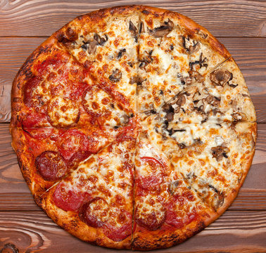 Pizza two in one, vegetarian mushroom and meat on a wooden table.