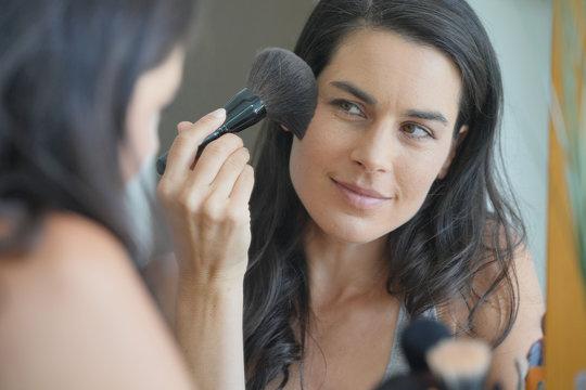 Portrait of brunette woman putting makeup on