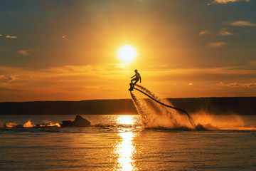 Poster Water Motor sporten Silhouette of a fly board rider over a river against the setting sun.