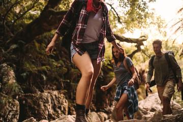 Friends trekking through a rocky trail in mountain