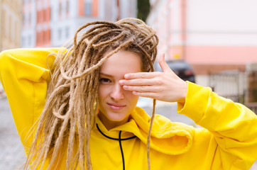 Portrait of young woman in yellow hoodie in the city street hiding one eye behind her hand
