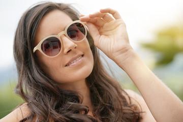 Portrait of smiling brunette woman wearing sunglasses