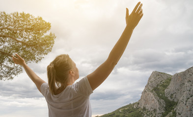 Woman with arms wide open enjoying views.