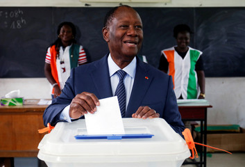President of Ivory Coast Alassane Dramane Ouattara of the RDR party casts his ballot during the country's municipal and regional elections in Abidjan