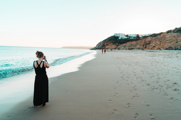 blonde woman take photo of the atlantic coast in Portugal - beach blue hour with rock cliffs in the background