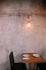 Contemporary dinner table and chair with old concrete wall and vintage lamp