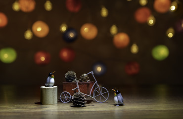 Two Penguins with tricycle with pine cone