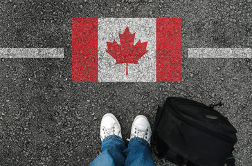 a man with a shoes and backpack is standing on asphalt nex to flag of Canada and border