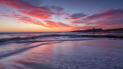 Sunrise over Dunstanburgh Castle on the coast of Northumberland, England, UK. Fototapete
