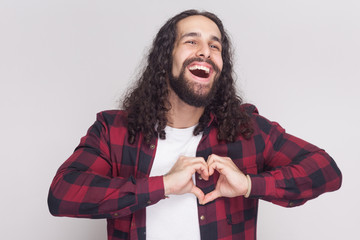 Portrait of happy in love handsome man with beard and black long curly hair in checkered red shirt standing, showing heart gesture with awesome emotion. indoor studio shot, isolated on grey background