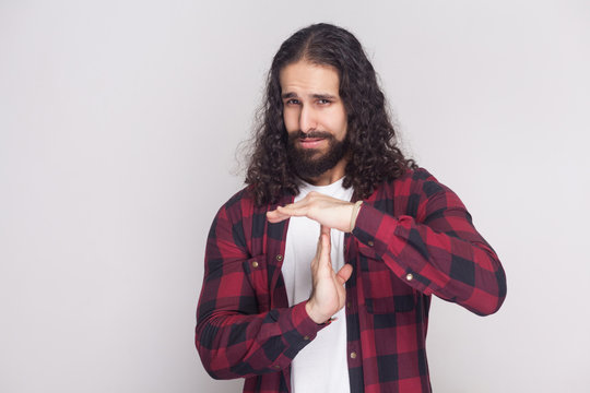 Please, i need more time. handsome man with beard and black long curly hair in checkered red shirt standing, looking at camera and showing timeout. indoor studio shot, isolated on grey background.