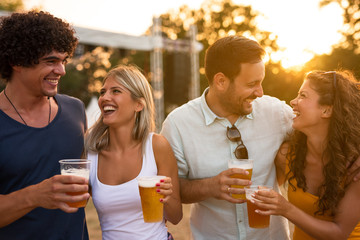 Enjoying beer with friends. Young people hanging out and enjoying drinks at music festival.