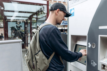 Tourist buys tickets for land or underground transport in Germany. Independent purchase of tickets for the tram, bus and train in a modern street machine.