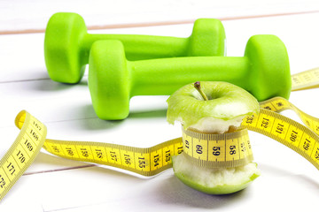 Green apples with measuring tape with green dumbbells on white wooden background.