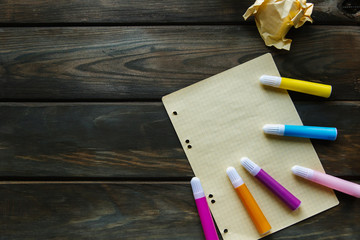 A clean sheet of paper and colored felt-tip pens lie on a wooden background, and crumpled sheets lie next